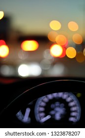 drive vehicle car travel road trip at city night with traffic light on street, image focus steering wheel and blur bokeh abstract background