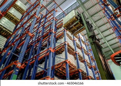drive-in racking system warehouse with reach-truck lifting a pallet for storage