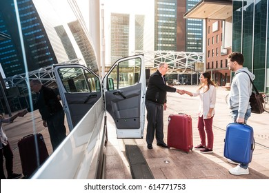 Driver of a airport shuttle minivan, greeting his passengers with their luggage on the sidewalk of a modern city business district