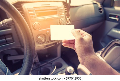 Driver In Car Hold A Blank Business Card Or License