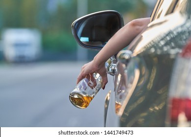 the driver of the car is holding a bottle of alcohol in his hands, a truck is driving towards him, drunkenness is driving