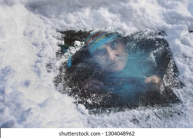 Driver in a car looking through a snow covered windshield