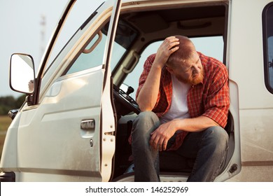 Driver of the car is sitting thinking about something