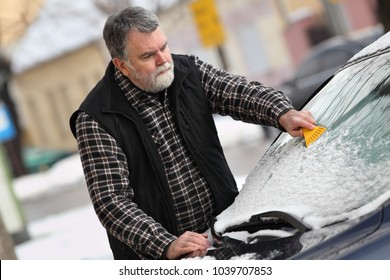 Driver cleaning snow from windshield of car using scraper
