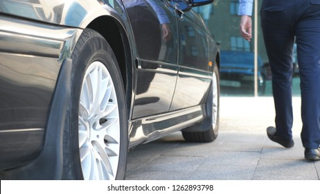 Driver coming to the car and opens the door for the businessman. Chauffeur uncover door of automobile for male passenger. Business man get out from the auto and leaves to office building. Slow Motion.