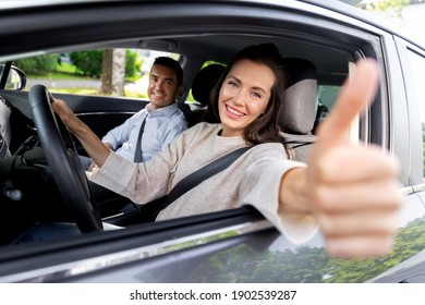 driver courses and people concept - car driving school instructor and young woman showing thumbs up to drive