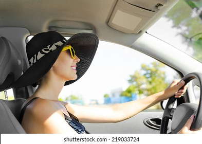 Driver in elegant hat driving a car