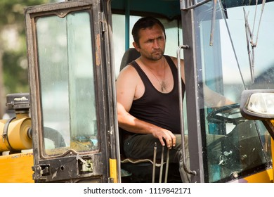 Driver - excavator driver in the cabin controls the process of moving the ground.
