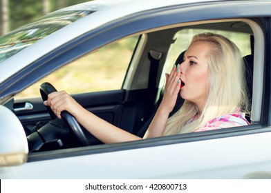 Driver girl yawns while driving a car