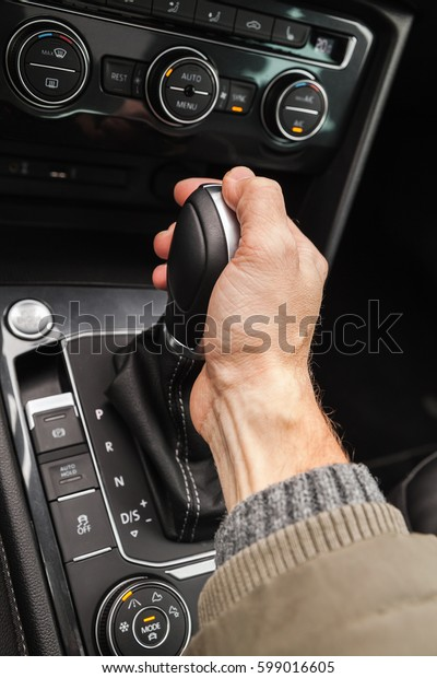 Driver hand holds gear lever of modern luxury crossover car. Close-up photo with selective focus