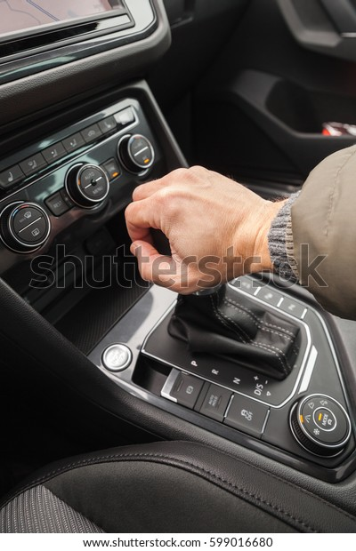Driver hand holds gear lever of modern luxury crossover car. Close up photo with selective focus