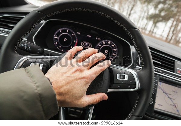 Driver hand pushes a steering wheel klaxon of luxury car. Closeup photo with selective focus