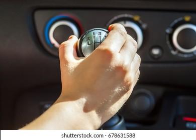Driver hand shifting gear shift knob manually, selective focus