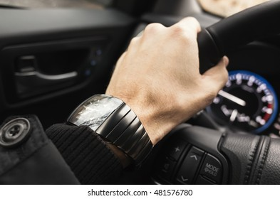 Driver hand with wrist watch on a steering wheel of luxury car. Closeup photo with selective focus
