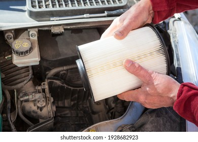 Driver hands inserting air filter paper cartridge inside plastic airbox of car engine, close-up view