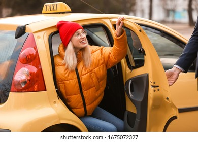Driver helping young woman to get out of taxi