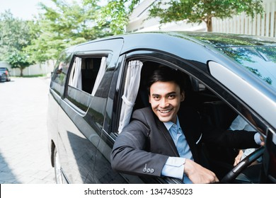 driver in his suit driving luxurious car. looking at camera
