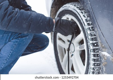 Driver is inflating a tire by car air compressor on the winter road.