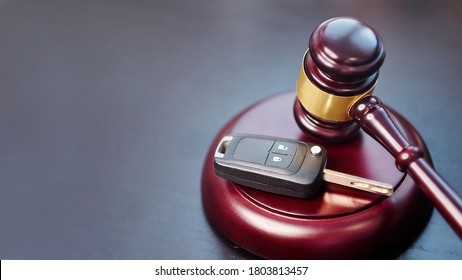 Driver license revocation concept next to the judge hammer. Traffic violation concept by car next to judge hammer. Revocable trust on a dark desk.