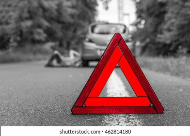 Driver lying under the broken car and traffic warning triangle - black and white concept