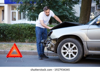 Driver man looking on wrecked car in car accident. Man regrets about fixing car after auto crash. Tragedy car collision. Dangerous road traffic situation