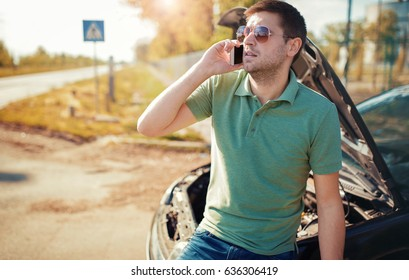 Driver on the road having problem with a car. Man calling for help with the mobile phone. Cars and transportation concept
