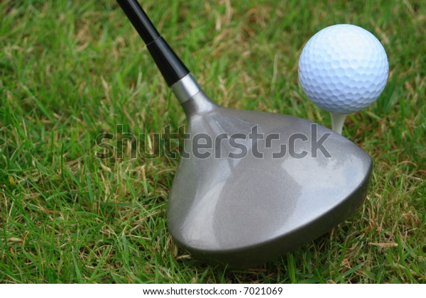 Driver or one wood and a golf ball on a tee peg on the teeing ground.