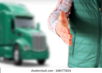 Driver with an open hand  greeting . Truck behind him