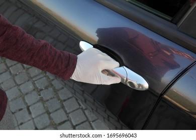 Führeröffnungstür des Autos mit Handschuhen auf Händen, Basisschutz von Coronavirus für die Person