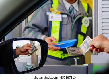 Driver paying a 1,000 Japanese Yen banknote for toll fees to an officer in Japan
