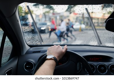 driver and a pedestrian at a crosswalk on rainy day