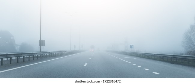 Driver POV on almost empty blue foggy misty rainy highway intercity road with low poor visibility on cold spring autumn morning. Seasonal bad rainy weather accident danger warning. car fog light
