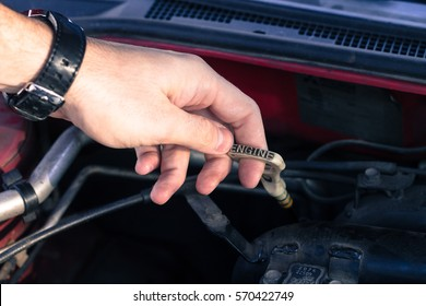 Driver pulls out an automobile dipstick to check the car's oil level.