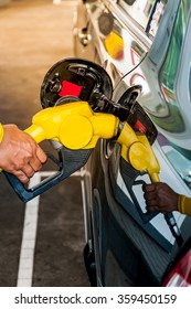 Driver pumping gasoline at the gas station, closeup