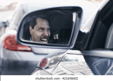 Driver with road rage reflected in wing mirror