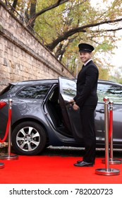 Driver standing near car on red carpet