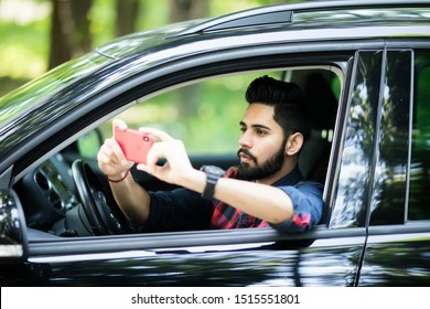 Driver taking photo with camera smartphone driving in car. Happy man taking picture with smart phone camera out window of car during travel road trip.
