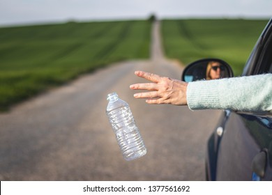Driver throwing away plastic bottle from car window on road. Environmental conservation. Plastic pollution concept