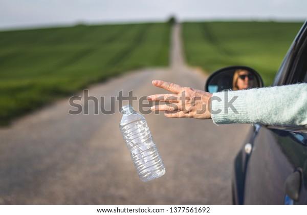 Le conducteur jette une bouteille de plastique depuis la fenêtre de la voiture sur la route. Conservation de l'environnement. Concept de pollution plastique
