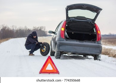 Driver took spare tire to change a flat one on winter road