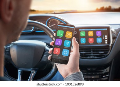 Driver uses a mobile phone with smart driving assistance apps. The app is connected to a car computer and is displayed on the board display.
