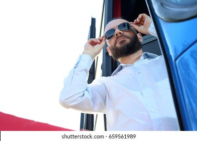 The driver waits for the passengers. A handsome bus driver in the bus