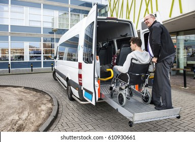 The driver of a wheel chair taxi, helping a disabled man in a wheel chair, using the lift in the back of his mini van