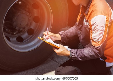 Driver worker handling clipboard check list and checking tire truck
