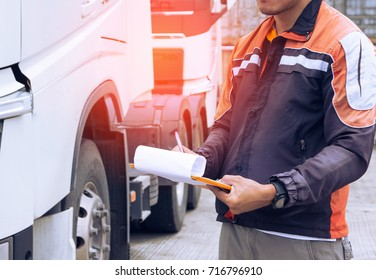 Driver worker handling clipboard and daily checking a truck before driving