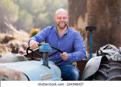 Driver working with tractor and smiling outdoor