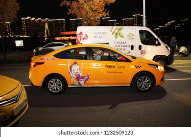 """Driver Yellow taxi car with a sticker from the cartoon """"Masha and the Bear"""" waving, the company Yandex taxi . Moscow. 26.10.2018"""