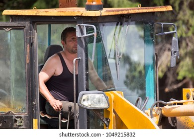 The driver-excavator driver in the cabin controls the process of moving the ground.  Work on the construction site. Digging trenches for laying communications to the building under construction.