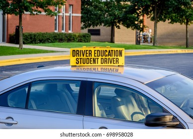 Drivers ed car in high school parking lot with bright yellow student driver sign on roof - logos removed