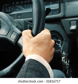 Driver's hand on steering wheel